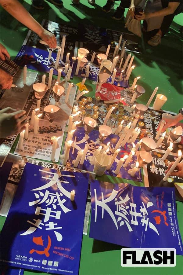 「中国共産党よ、滅びろ」と書かれたポスターにロウソクを供える